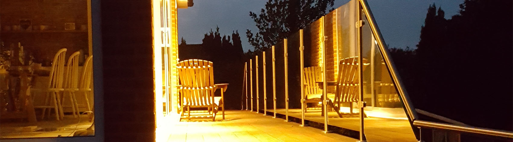 Glass balustrade installed on decking and shown at night time